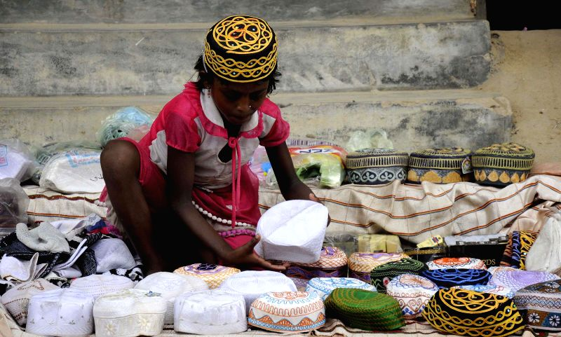 A child arranges cap at her make-shift stall of prayer caps on the eve of Eid-ul-Fitr at a market place in Sonamura, 59 kms south of Agartala on July 28, 2014.