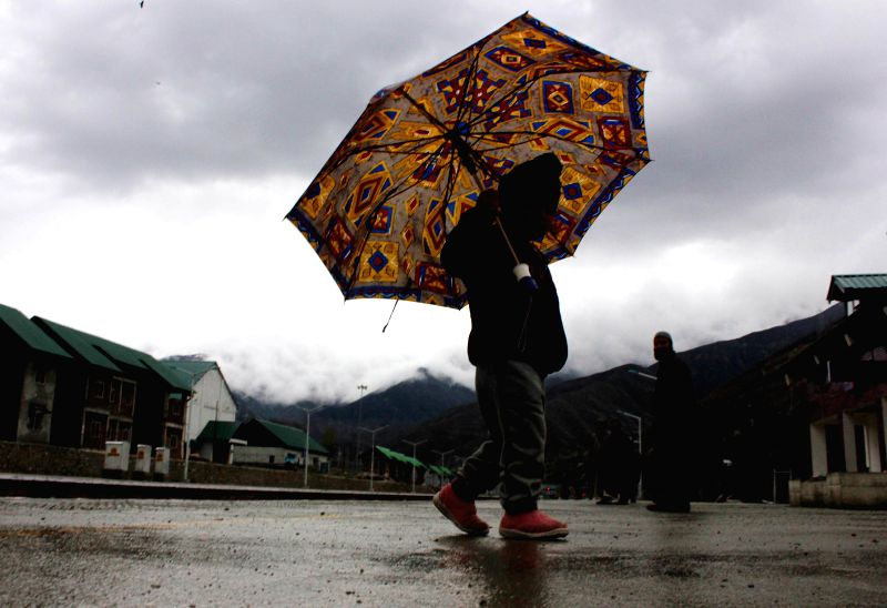 A child carries an umbrella as it rains in Srinagar on April 18, 2014.