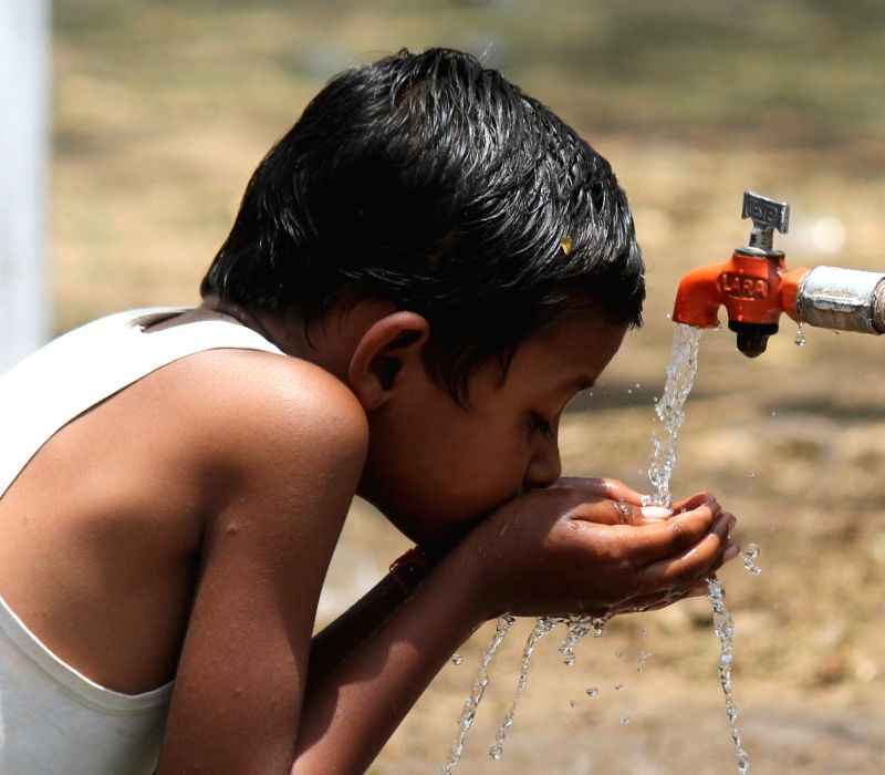A child drinks water from a tap on a hot day in Nagpur on April 20, 2017.