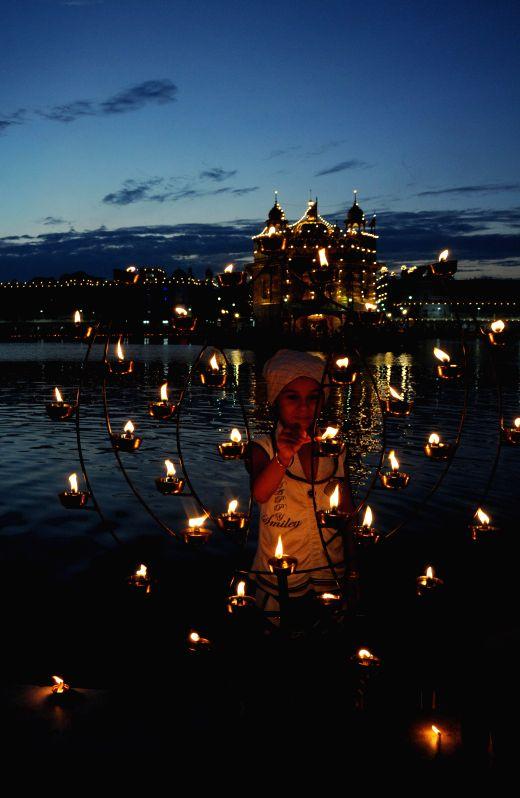 A child lights up candles at the Golden Temple on Parkash Utsav of Sri Guru Granth Sahib (410th anniversary of installation of the Guru Granth Sahib) in Amritsar on Sept 1, 2014.
