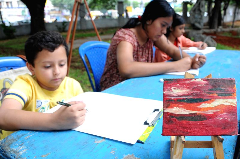 """A child paints at """"Art Park - Bangalore"""" - spot painting, exhibition and sale at Ravindra Kalakshetra in Bangalore on July 6, 2014."""