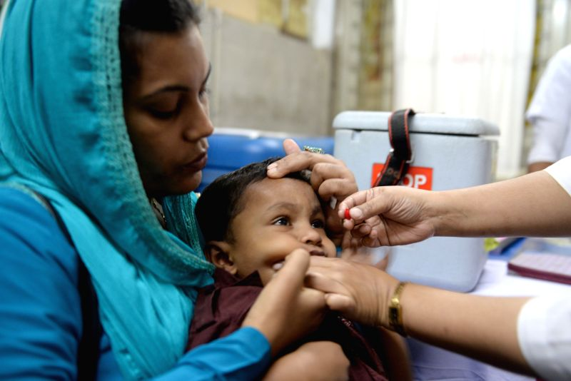 A child receives vitamin A capsules from a health worker during a vitamin A campaign at Dhaka Medical College Hospital in Dhaka, Bangladesh, Nov. 14, 2015. ...
