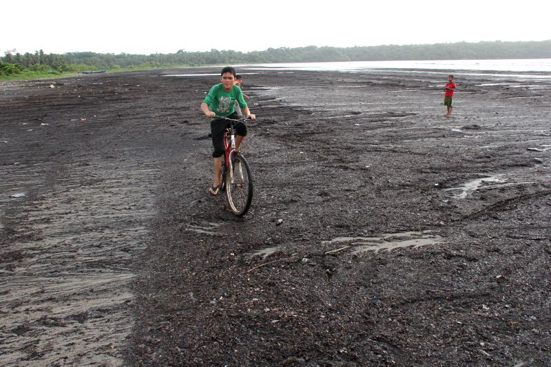 A child rides a cycle on a dirty beach as waves deposited a large amount of waste at Caranzalem, near Panaji on Aug 16, 2014.