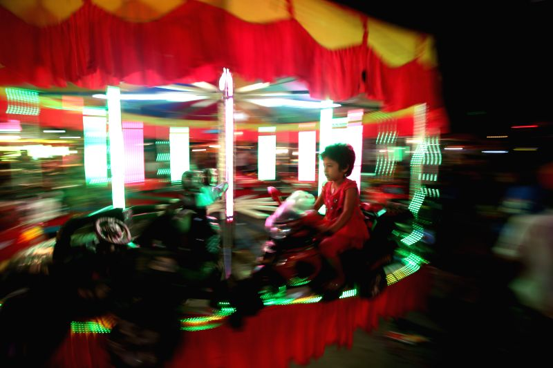 A child rides merry-go-round during the Thadingyut Festival in Yangon, Myanmar, Oct. 28, 2015. The Thadingyut lantern festival is held on the full moon day of the ...