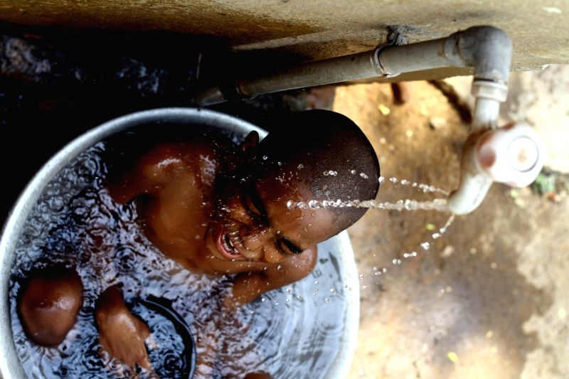 A child sits under a tap to beat the heat in Chennai on May 18, 2017.