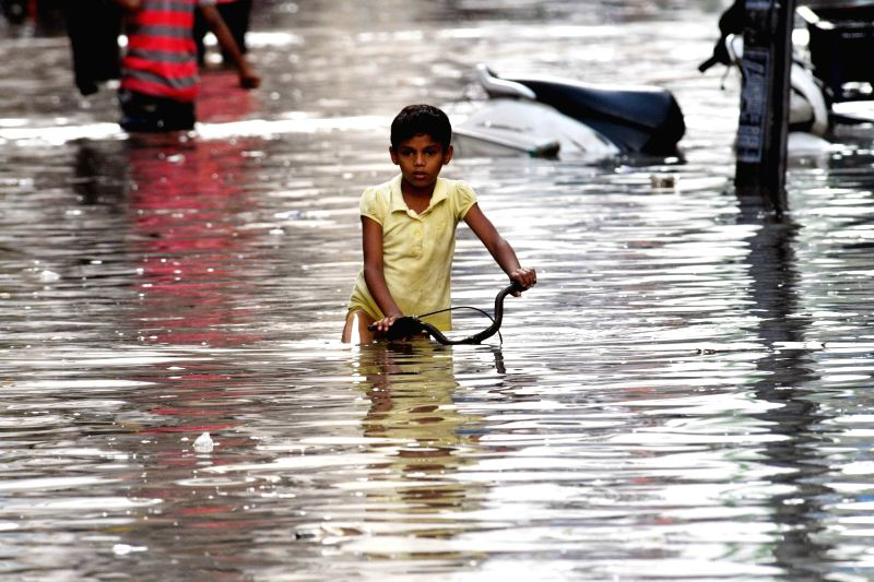A child struggles through a water-logged street after heavy rains, in Patna on July 26, 2018.
