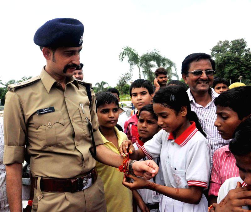A child ties `rakhi` on the wrist of Patna Senior Superintendent of Police Manu Maharaj on `Raksha Bandhan` in Patna on Aug 10, 2014.