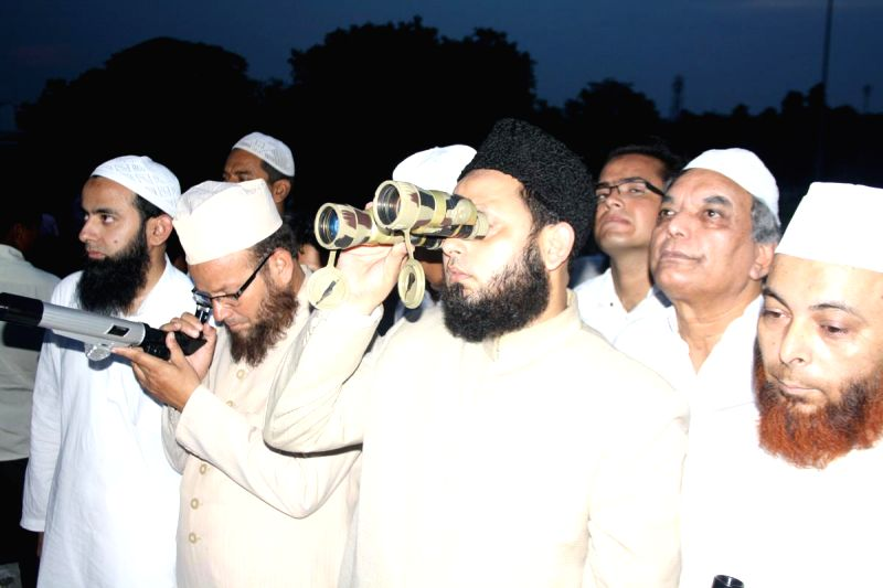 A cleric tries to get a glimpse of the sliver of the moon at Eidgah in Lucknow on July 28, 2014.