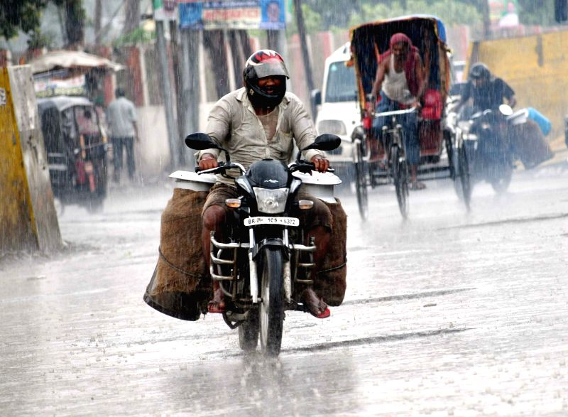 A commuter during rains, in Patna on June 12, 2018.