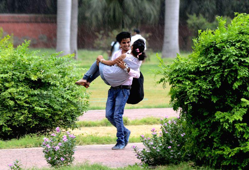 A couple enjoys the rain in New Delhi on June 23, 2015.