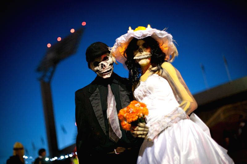 """A couple pose with costumes during the """"Megaofrenda 2015"""" organized by the National Autonomous University of Mexico to mark the Day of the Dead at ..."""
