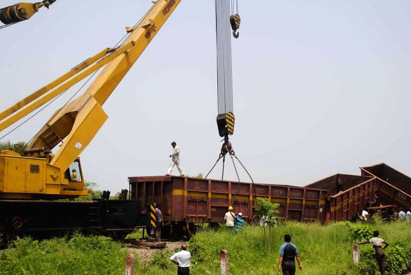 A crane lifts the coaches of goods train which jumped tracks near Motihari in East Champaran district of Bihar on June 25, 2014.