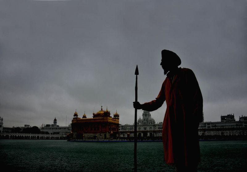 A devotee at the Golden Temple during rains in Amritsar on July 17, 2014.