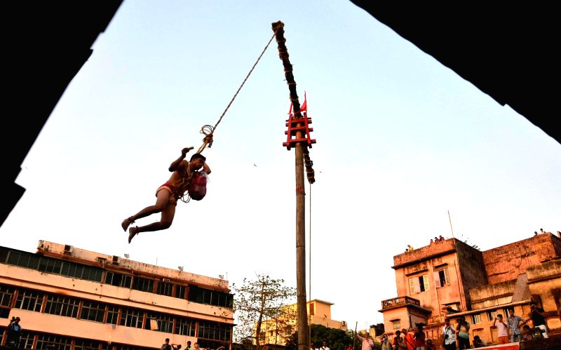 A devotee hangs from a pole during Charak festival in Kolkata on April 14, 2017.