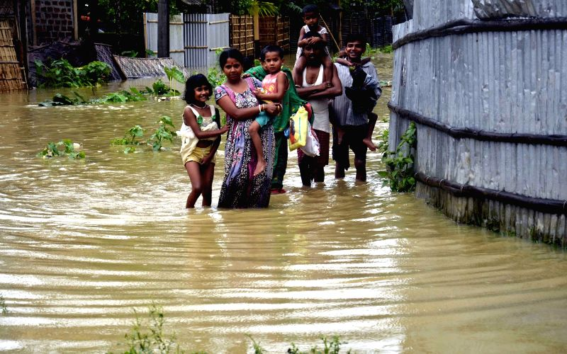 A family wades through a flooded road towards higher land in Dharmanagar after incessant rain in Tripura on May 18, 2016.