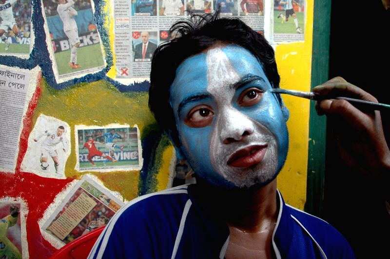 A fan of Argentina football team painting his face in Kolkata on July 5, 2014.