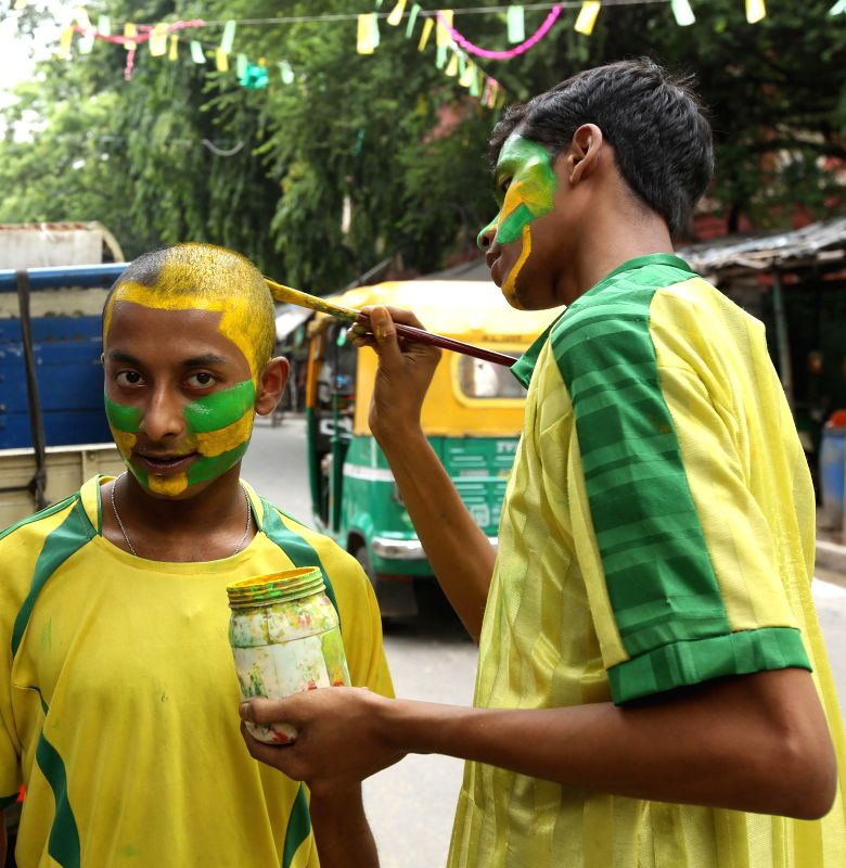 A fan of Brazilian football team gets his face painted in the team's colour in Kolkata on July 8, 2014.