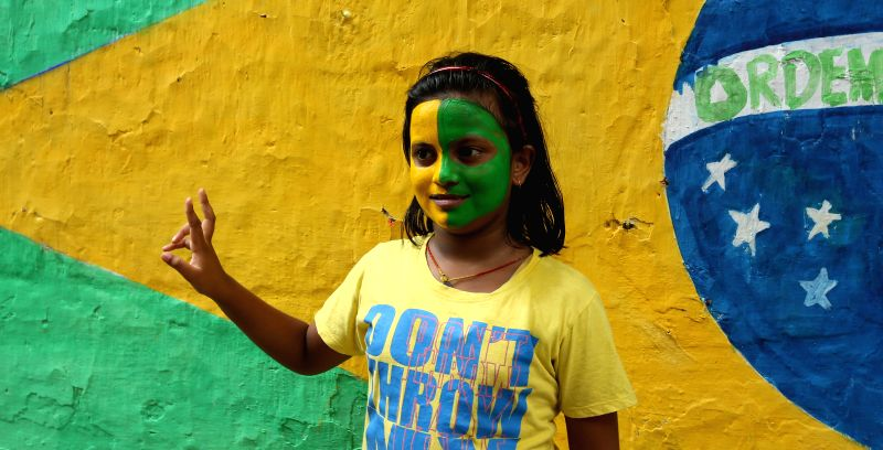 A fan of Brazilian football team with her face painted in team's colour in Kolkata on July 8, 2014.