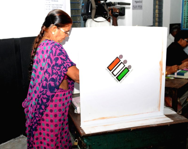 A female voter casting her vote, at a polling booth, during the Puducherry Assembly Election, on May 16, 2016.