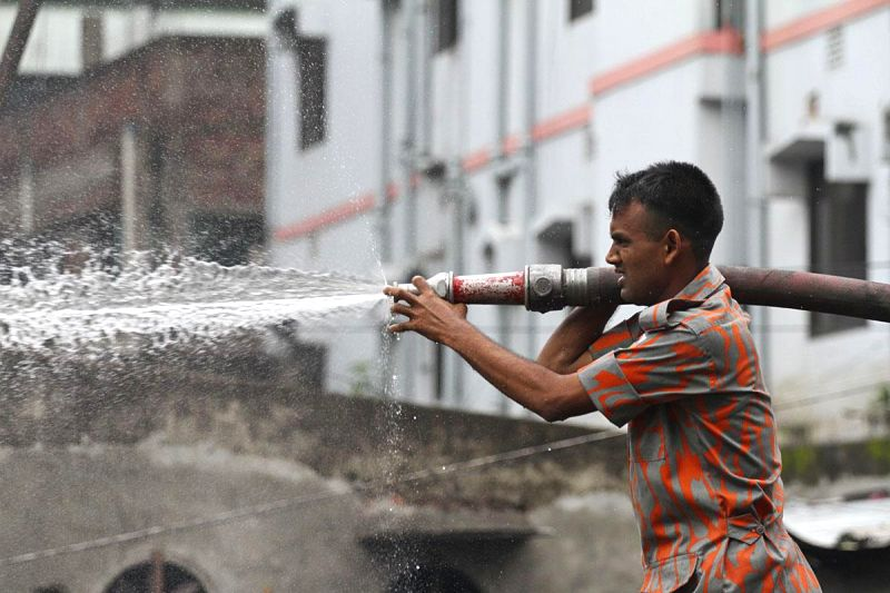 A firefighter tries hard to douse a fire that broke out at a chemical warehouse in Swarighat area of Dhaka, Bangladesh on Aug 13, 2014.