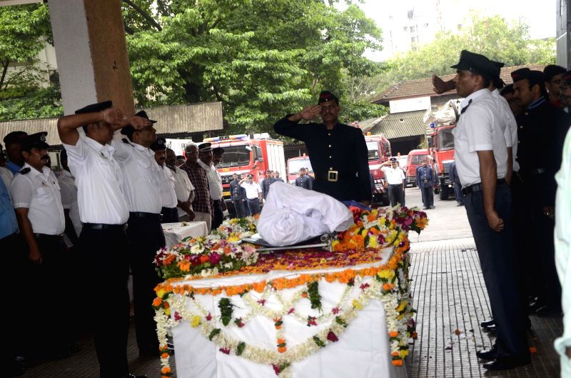 A fireman pays his last respect to his colleague Nitin Yevlekar who was killed dousing flames at the 22-storeyed Lotus Park building where a fire broke out yesterday (18th July 2014), at Fire Brigade