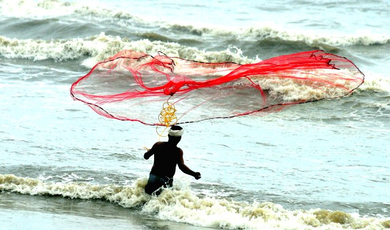 A fisherman casts his net on the Payyambalam beach in Kannur, Kerala on June 19, 2016.