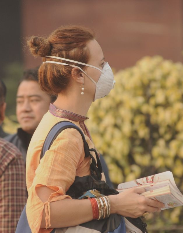 A foreign tourist wears a mask as fog blankets the capital on Dec 30, 2017.(Image Source: IANS)