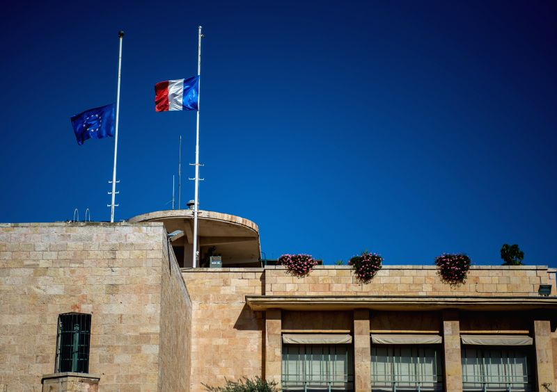 A French national flag and an European Union flag fly at half mast at Consulate General of France in Jerusalem to mourn the victims of a series of attacks in ...