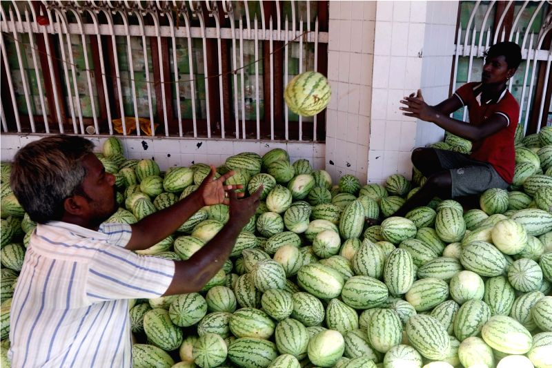 A fruit seller sits on a stack of watermelons - the demand for which shoots up during summers - as he arranges them, at a market in Chennai on March 16, 2018.