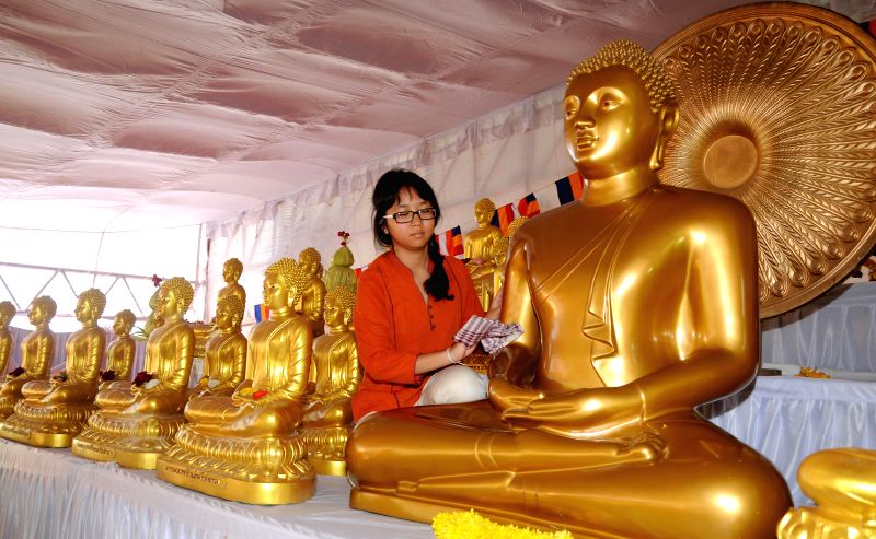 A girl cleans the Buddha statue during a programme in Bangalore on Aug 10, 2014.