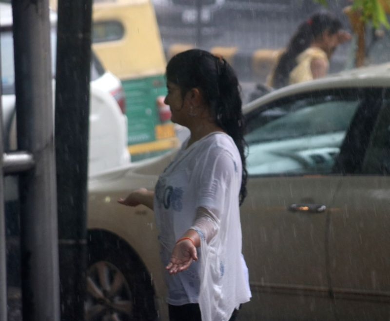 A girl enjoys herself during rains in New Delhi on July 16, 2018.