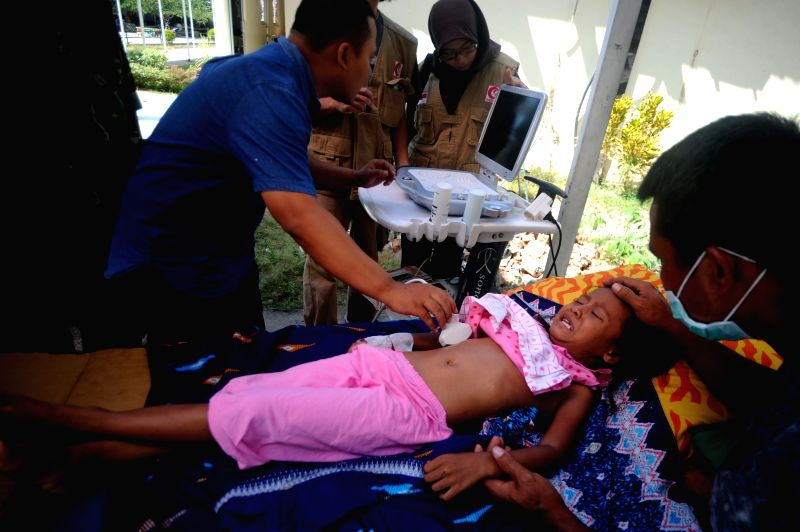 A girl receives treatment at a temporary tent at a hospital in North Lombok, West Nusa Tenggara, Indonesia, on Aug. 7, 2018. Death toll from Sunday's ...