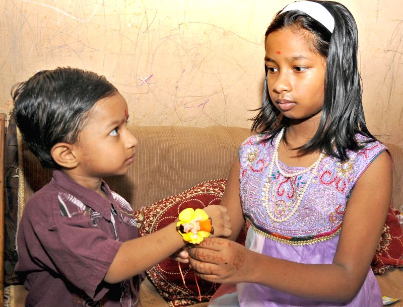 A girl ties a `rakhi` on the wrist of her brother on 'Raksha Bandhan' in New Delhi on Aug 10, 2014.