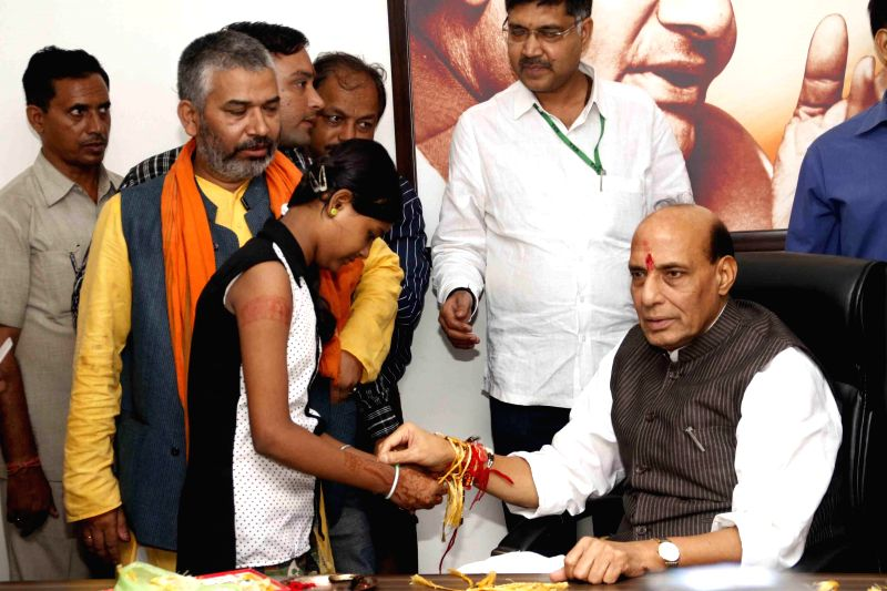 A girl ties a `rakhi` on the wrist of Union Home Minister Rajnath Singh on the occasion of Raksha Bandhan in New Delhi on Aug 10, 2014.