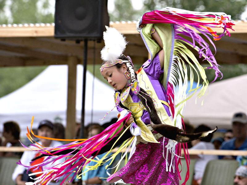A girl wearing traditional costume dances during the Echos of a Nation powwow at the Kahnawake reserve near Montreal, Canada, on July 11, 2015. The powwow is ...