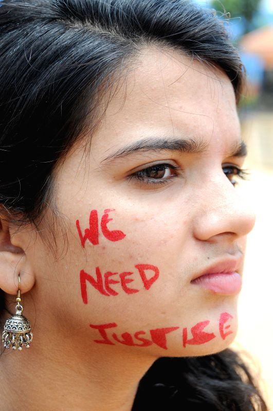A girl with a message painted on her face reading 'we need justice' participates in a demonstration against  crime against women in Bangalore on July 20, 2014.