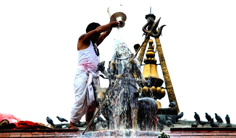 A Hindu priest pours milk to the idol of Lord Shiva while offering prayers at the Shiva temple in Kathmandu, Nepal, Aug. 1, 2015. The Shrawan month is considered ...