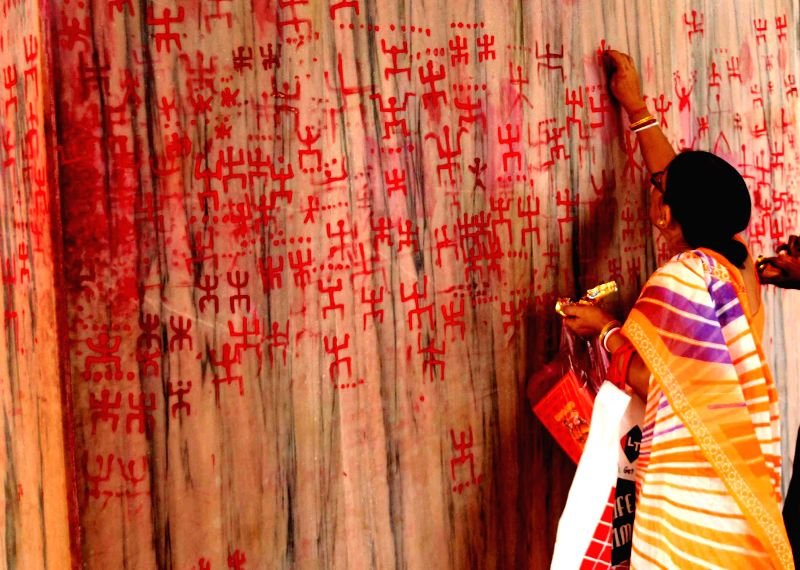 A Hindu woman draws 'swastik' symbols which are considered as auspicious on `Poila Baisakh`in a temple of Agartala on April 15, 2014. Poila Baisakh is the first day of the Bengali calendar which is ..