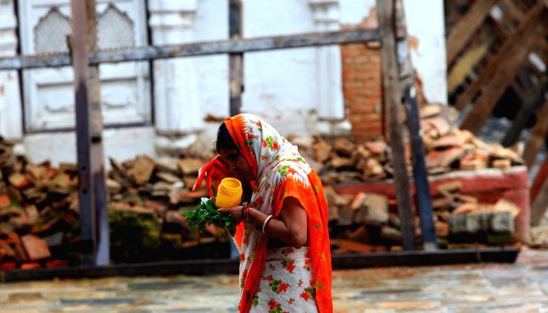 A Hindu woman returns after offering prayers on Shrawan Somvar near Shiva temple in Kathmandu, Nepal, Aug. 3, 2015. Shrawan Somvar (Monday) is considered ...