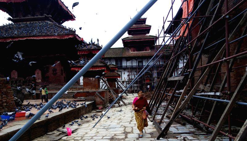 A Hindu woman walks to offer prayers on Shrawan Somvar near Shiva temple in Kathmandu, Nepal, Aug. 3, 2015. Shrawan Somvar (Monday) is considered auspicious for ...