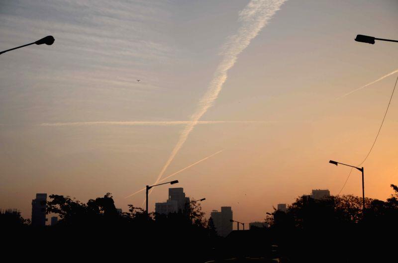 A jet creates patterns in the orange-tinged skies of Mumbai during sunrise on Feb 10, 2018.