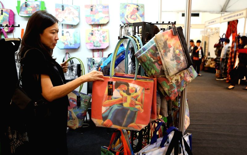 A journalist selects handmade bags at the media centre of Asia Pacific Economic Cooperation (APEC) summit in Manila, the Philippines, Nov. 17, 2015. Over 20 ...