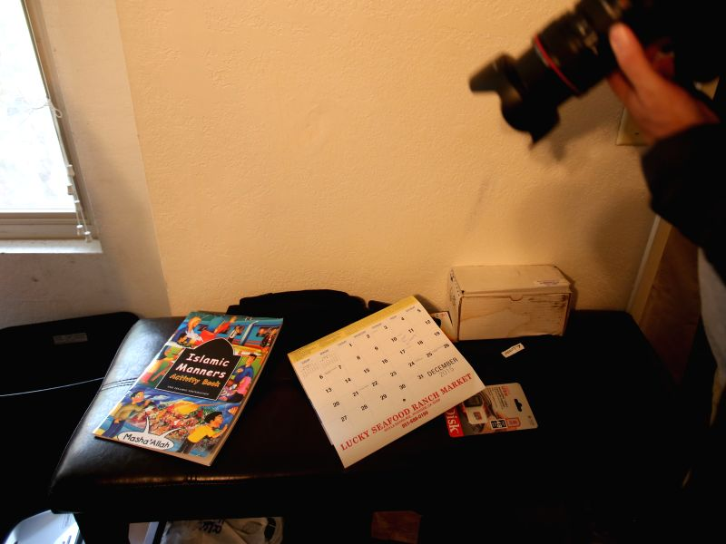 A journalist takes photos of a comic book on religious manners in the residence of shooting suspect Syed Farook in San Bernardino, California, Dec. 4, 2015. ...