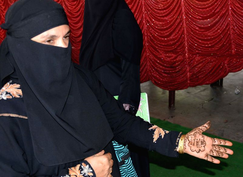 A lady applying Mehndi on the palm of a Muslim women with polling dates written as part of voter awarness programm at Kareemnagar district in Andhra Pradesh on April 26, 2014.