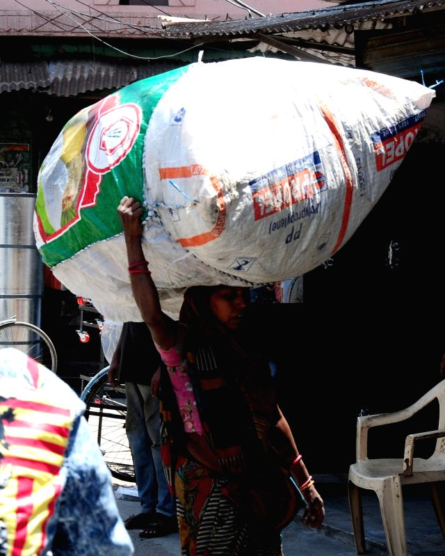 A lady carries load on her head in Amritsar on May 1, 2017. May 1 is observed as International Workers' Day.