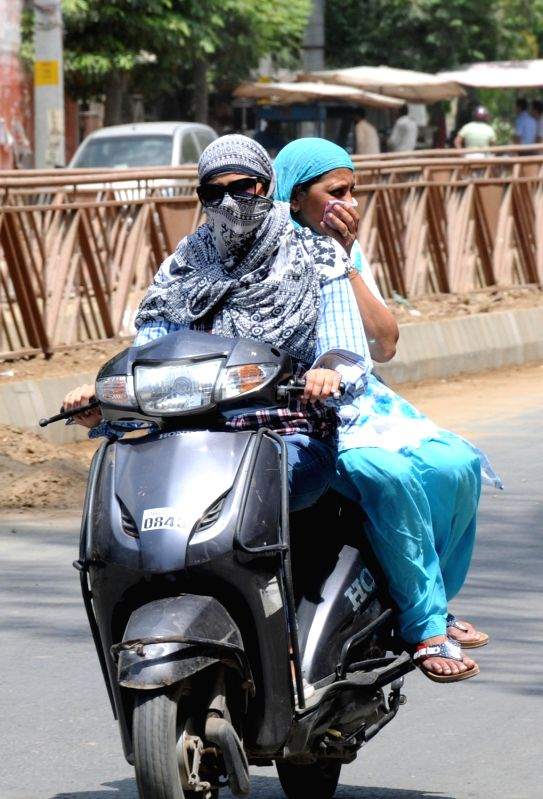 A lady covers her face to avoid scorching sun on a hot day in Amritsar on May 16, 2016.