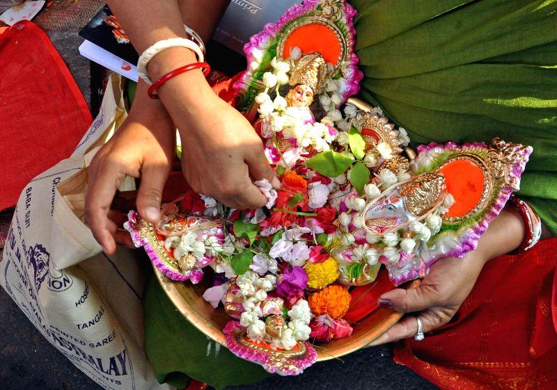 A lady holds idols of lord Ganesh and goddess Lakshmi during `Poila Baisakh` at Kalighat in Kolkata on April 15, 2014.