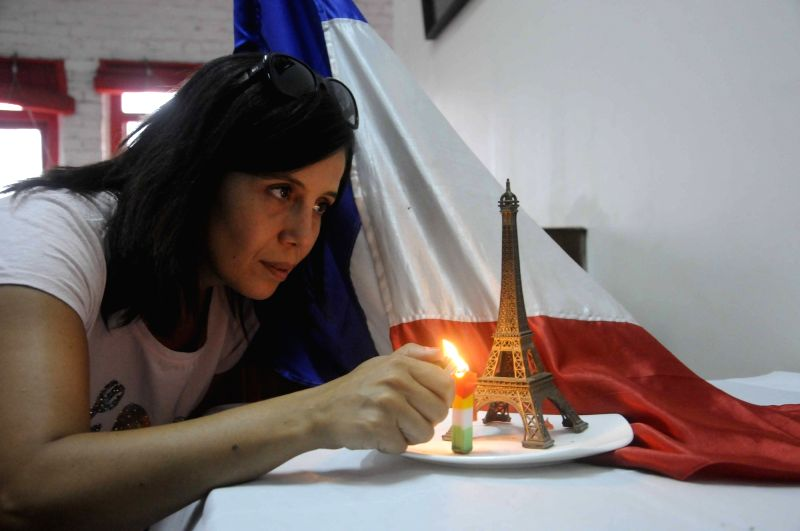 A lady lights a candle to show solidarity with the victims of 13/11 Paris blasts in Kolkata, on Nov 16, 2015.