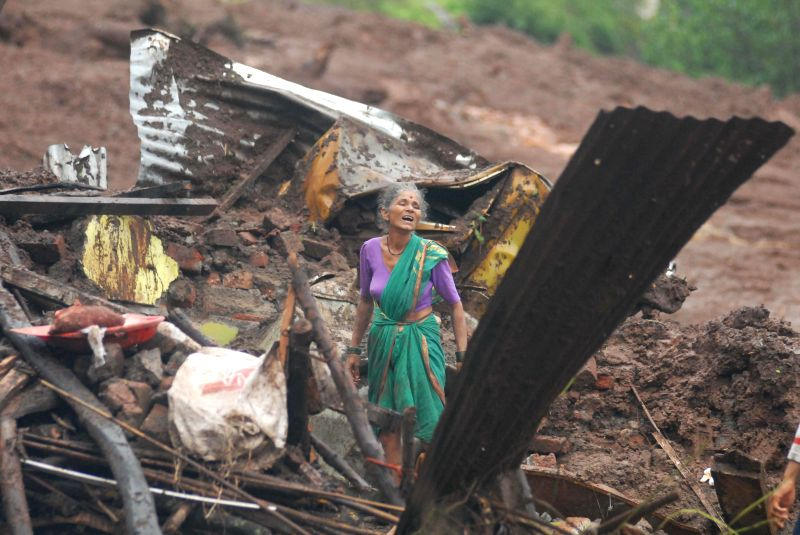 A lady looks at the debris of her house in Malin village after a hillock crashed on the village near Pune early Wednesday (30th July, 2014) morning; on July 31, 2014. At least 25 people were killed ..