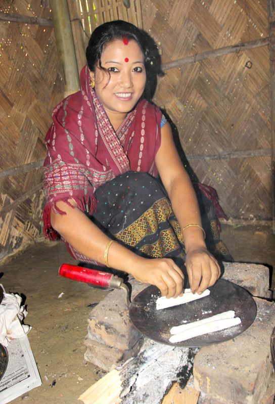 A lady prepares rice cakes on Bohag Bihu at Tengakhat village in Dibrugarh  district of Assam on April 14, 2014.